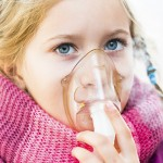 Young girl with asthma uses inhaler
