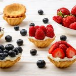 Tartlets with cream, blueberries, raspberries and strawberries on white wooden table. Selective focus.