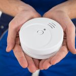 Close-up Of Male Electrician Hand Holding Smoke Detector