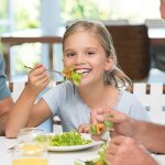 Cheerful little girl enjoying lunch with her family. Portrait of a happy smiling daughter eating salad for lunch and looking at camera. Happy female child having lunch with extended family at home.