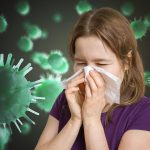 Ill woman has flu and is sneezing. Many viruses and germs flying around.